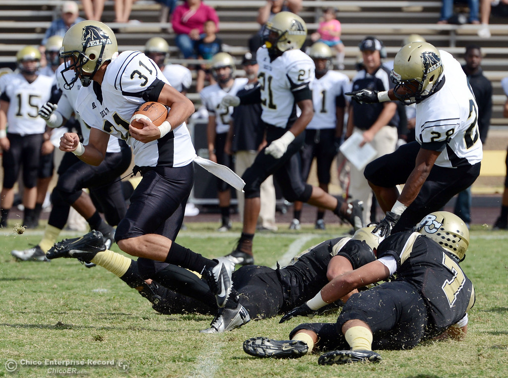 Description of . Delta College's #31 Brian Wood (left) breaks tackles by Butte College in the second quarter of their football game at Butte's Cowan Stadium Saturday, September 28, 2013, in Oroville, Calif.  (Jason Halley/Chico Enterprise-Record)