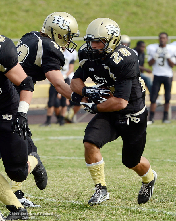 Description of . Butte Colleges\' #20 Armand Bokitch (right) carries against Delta College in the fourth quarter of their football game at Butte\'s Cowan Stadium Saturday, September 28, 2013, in Oroville, Calif.  (Jason Halley/Chico Enterprise-Record)