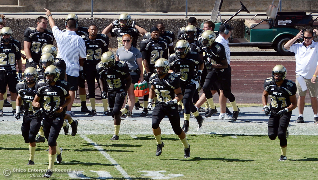 Description of . Butte College takes the field against Delta College in the first quarter of their football game at Butte's Cowan Stadium Saturday, September 28, 2013, in Oroville, Calif.  (Jason Halley/Chico Enterprise-Record)