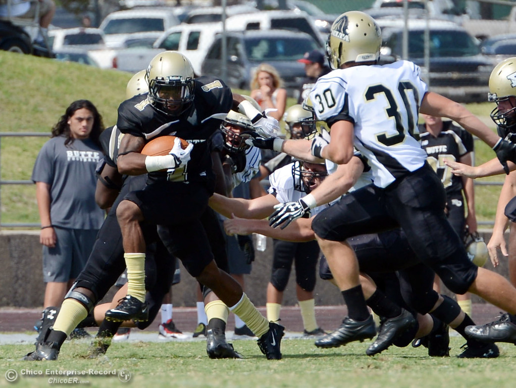 Description of . Butte College\'s #1 Wes McCoy (left) rushes against Delta College in the second quarter of their football game at Butte\'s Cowan Stadium Saturday, September 28, 2013, in Oroville, Calif.  (Jason Halley/Chico Enterprise-Record)