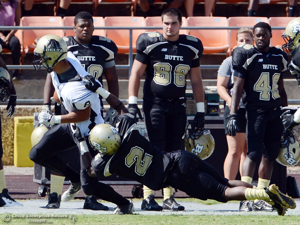 Description of . Butte College\'s #2 Deonte Flemings (right) tackles against Delta College\'s #8 William Mafi (left) in the first quarter of their football game at Butte\'s Cowan Stadium Saturday, September 28, 2013, in Oroville, Calif.  (Jason Halley/Chico Enterprise-Record)