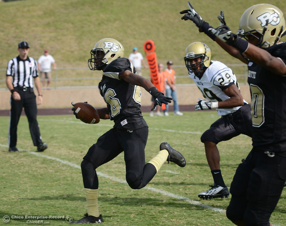 Description of . Butte College's #86 Jon Parks (left) rushes for a touchdown against Delta College's #29 Damien Bell-White (center) as Butte's #10 CJ Grice (right) reacts in the fourth quarter of their football game at Butte's Cowan Stadium Saturday, September 28, 2013, in Oroville, Calif.  (Jason Halley/Chico Enterprise-Record)
