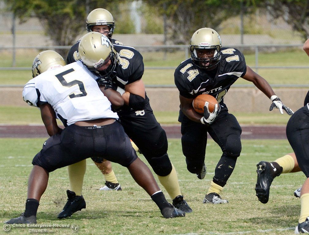 Description of . Butte College\'s #14 Robert Frazier (right) rushes on a block by #30 Eric DeLucchi (center) against Delta College\'s #5 DaShaun Perkins (left) in the second quarter of their football game at Butte\'s Cowan Stadium Saturday, September 28, 2013, in Oroville, Calif.  (Jason Halley/Chico Enterprise-Record)