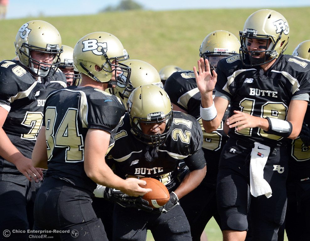 Description of . Butte College's #21 Marvel Harris (center) is congratulated for a touchdown against Delta College in the fourth quarter of their football game at Butte's Cowan Stadium Saturday, September 28, 2013, in Oroville, Calif.  (Jason Halley/Chico Enterprise-Record)