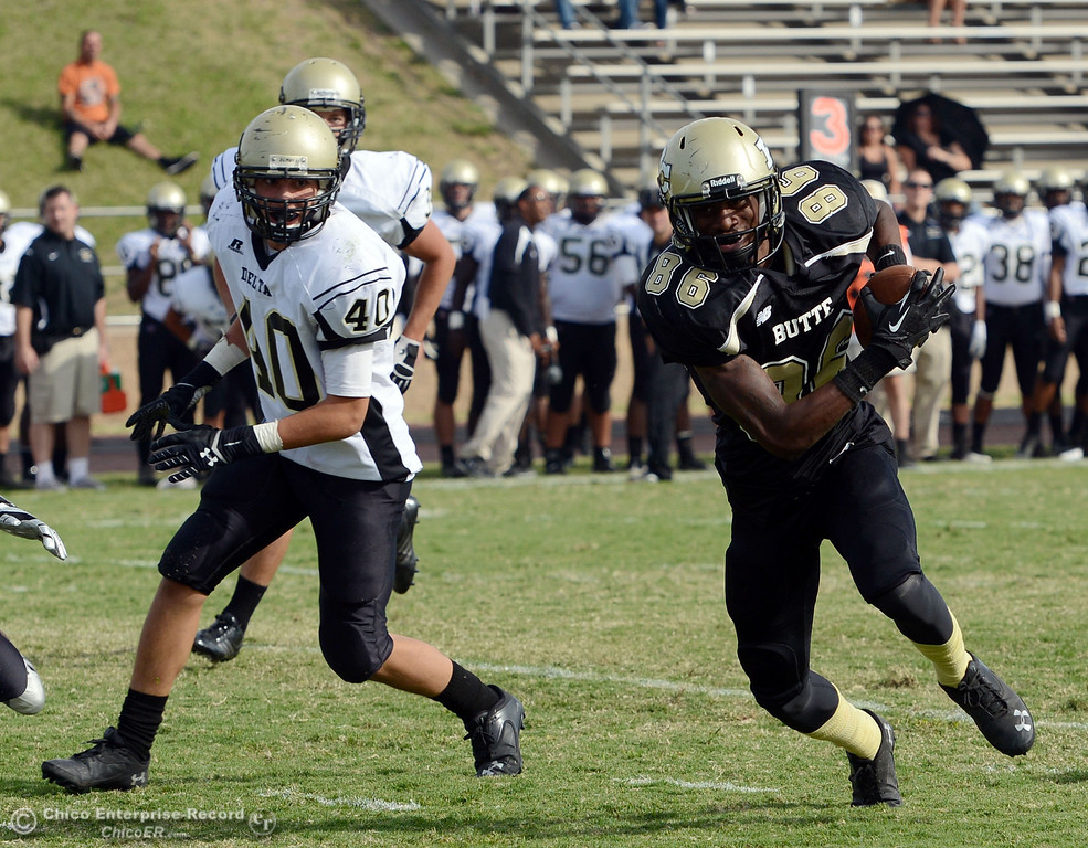 Description of . Butte College's #86 Jon Parks (right) rushes for a touchdown against Delta College's #40 Adrian Ramos (left) in the fourth quarter of their football game at Butte's Cowan Stadium Saturday, September 28, 2013, in Oroville, Calif.  (Jason Halley/Chico Enterprise-Record)