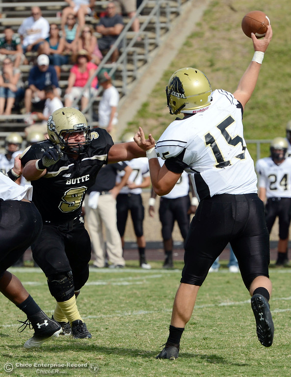 Description of . Butte College's #9 Tyler Adair (left) pressures against Delta College's #15 Cody Weinzheimer (right) in the third quarter of their football game at Butte's Cowan Stadium Saturday, September 28, 2013, in Oroville, Calif.  (Jason Halley/Chico Enterprise-Record)
