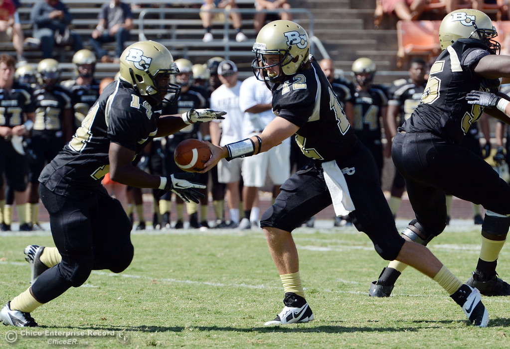Description of . Butte College's #12 Thomas Stuart (right) hands off to #14 Robert Frazier (left) against Delta College in the first quarter of their football game at Butte's Cowan Stadium Saturday, September 28, 2013, in Oroville, Calif.  (Jason Halley/Chico Enterprise-Record)