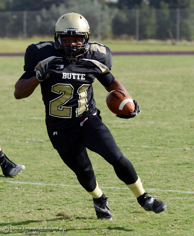 Description of . Butte College\'s #21 Marvel Harris rushes against Delta College in the fourth quarter of their football game at Butte\'s Cowan Stadium Saturday, September 28, 2013, in Oroville, Calif.  (Jason Halley/Chico Enterprise-Record)