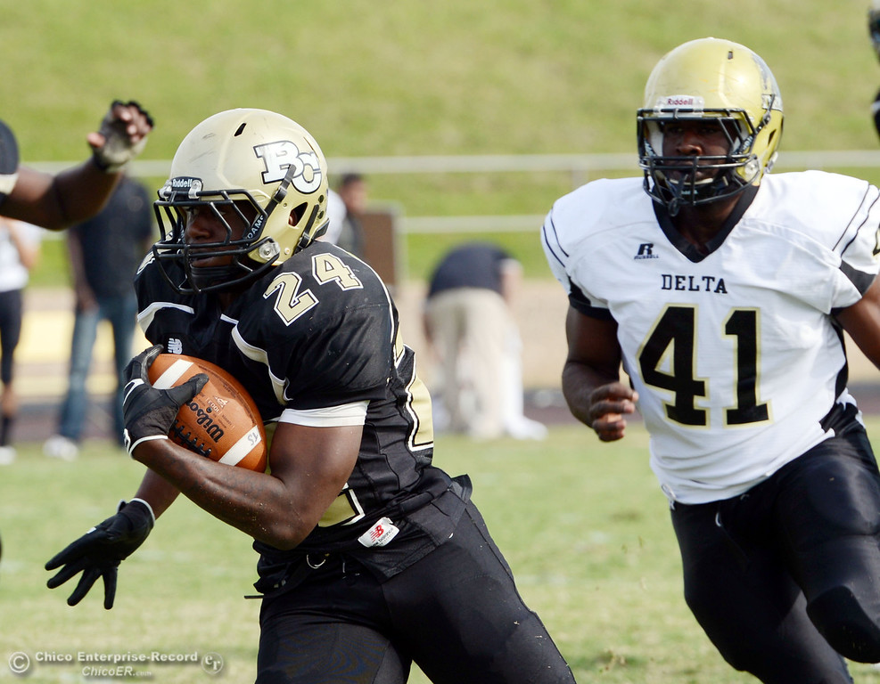 Description of . Butte College's #24 Kendall Williams (left) rushes against Delta College's #41 Richard Black (right) in the fourth quarter of their football game at Butte's Cowan Stadium Saturday, September 28, 2013, in Oroville, Calif.  (Jason Halley/Chico Enterprise-Record)