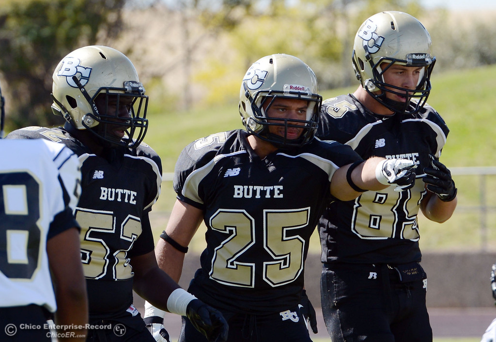 Description of . Butte College\'s #52 Kyjuan Tate, #25 De\'Aundray Gooden, and #85 Richard Murphy (left to right)  against Delta College in the first quarter of their football game at Butte\'s Cowan Stadium Saturday, September 28, 2013, in Oroville, Calif.  (Jason Halley/Chico Enterprise-Record)