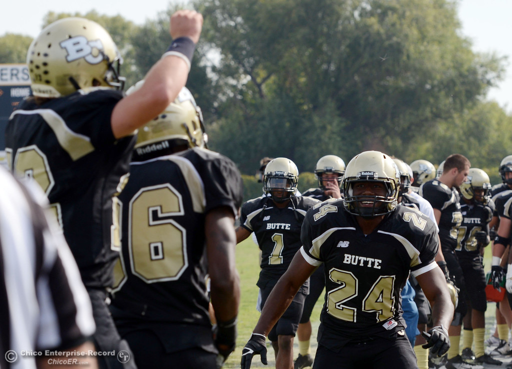 Description of . Butte College's #24 Kendall Williams (right) celebrates the team scoring a touchdown against Delta College in the fourth quarter of their football game at Butte's Cowan Stadium Saturday, September 28, 2013, in Oroville, Calif.  (Jason Halley/Chico Enterprise-Record)
