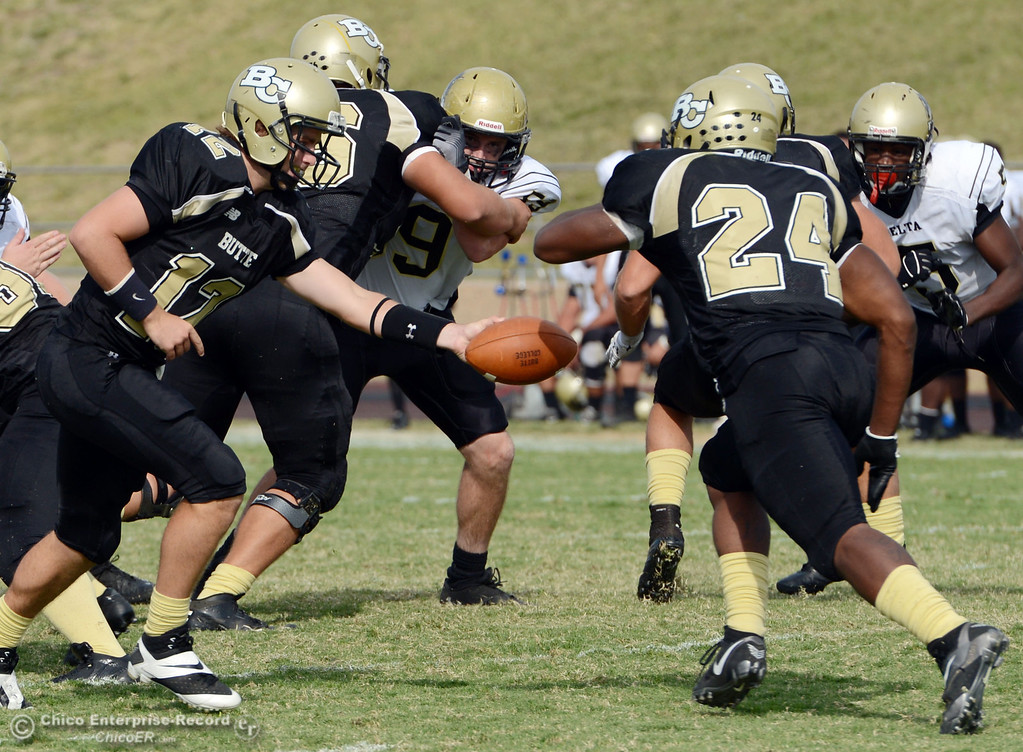 Description of . Butte College #12 Thomas Stuart (left) hands off to #24 Kendall Williams (right)  against Delta College in the fourth quarter of their football game at Butte's Cowan Stadium Saturday, September 28, 2013, in Oroville, Calif.  (Jason Halley/Chico Enterprise-Record)