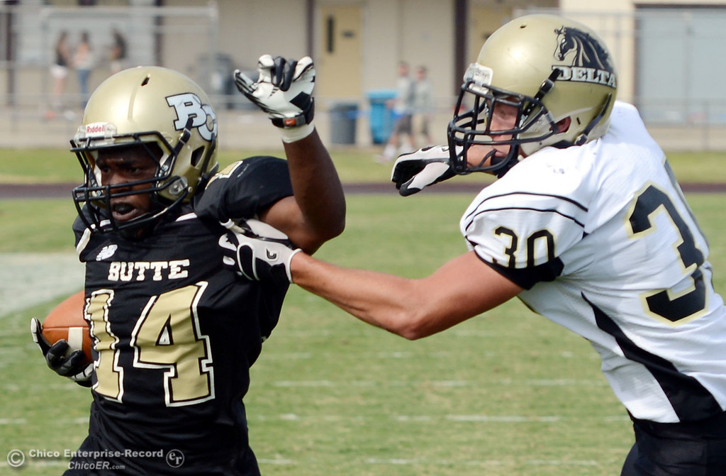 Description of . Butte Colleges\' #14 Robert Frazier (left) is tackled against Delta College\'s #30 Andrew Truaz (right ) in the third quarter of their football game at Butte\'s Cowan Stadium Saturday, September 28, 2013, in Oroville, Calif.  (Jason Halley/Chico Enterprise-Record)