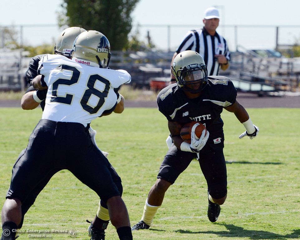 Description of . Butte College's #1 Wes McCoy (right) rushes against Delta College in the first quarter of their football game at Butte's Cowan Stadium Saturday, September 28, 2013, in Oroville, Calif.  (Jason Halley/Chico Enterprise-Record)