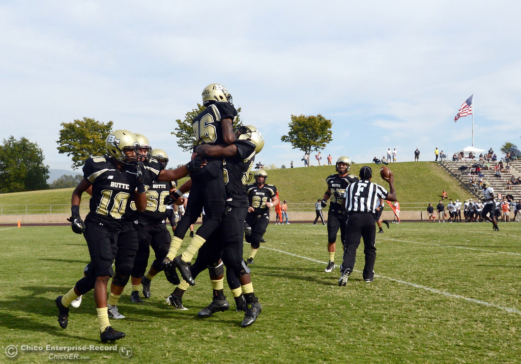 Description of . Butte College's #86 Jon Parks (center) is lifted by #55 Dominique Harris (right) as the team congratulates Parks on a touchdonw against Delta College in the fourth quarter of their football game at Butte's Cowan Stadium Saturday, September 28, 2013, in Oroville, Calif.  (Jason Halley/Chico Enterprise-Record)