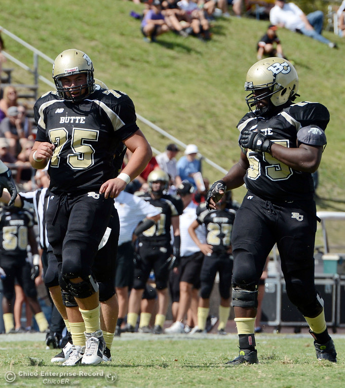 Description of . Butte College's #75 Jacob Vazquez (left) and #55 Dominique Harris (right) against Delta College in the second quarter of their football game at Butte's Cowan Stadium Saturday, September 28, 2013, in Oroville, Calif.  (Jason Halley/Chico Enterprise-Record)