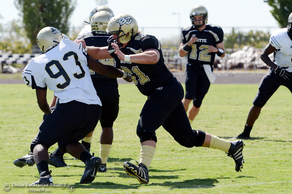 Description of . Butte College's #61 Jacob Bigham (right) blocks against Delta College's #93 Marcus Brown (left) in the first quarter of their football game at Butte's Cowan Stadium Saturday, September 28, 2013, in Oroville, Calif.  (Jason Halley/Chico Enterprise-Record)