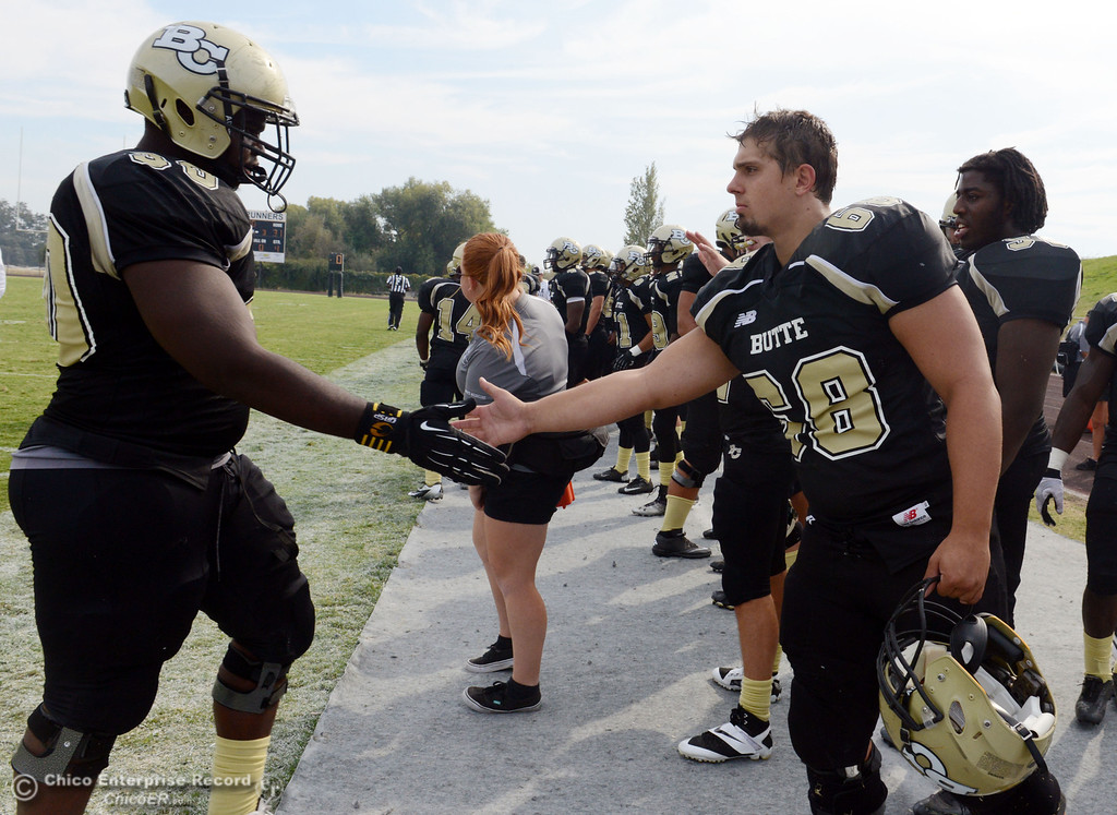 Description of . Butte College's #90 Stephen Francois (left) and #68 Eli Thom (right) shake hands against Delta College in the fourth quarter of their football game at Butte's Cowan Stadium Saturday, September 28, 2013, in Oroville, Calif.  (Jason Halley/Chico Enterprise-Record)