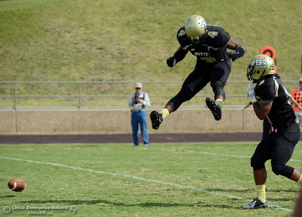 Description of . Butte College's #4 Chris Edwards (left) reacts to coming up short on a interception attempt next to #3 London Muse (right) against Delta College in the second quarter of their football game at Butte's Cowan Stadium Saturday, September 28, 2013, in Oroville, Calif.  (Jason Halley/Chico Enterprise-Record)