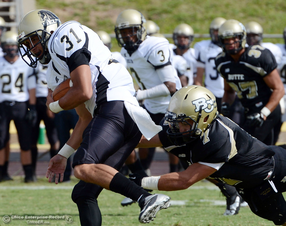 Description of . Butte College's #7 Ryan Holland (right) attempts to tackle against Delta College's #31 Brian Wood (left) in the second quarter of their football game at Butte's Cowan Stadium Saturday, September 28, 2013, in Oroville, Calif.  (Jason Halley/Chico Enterprise-Record)