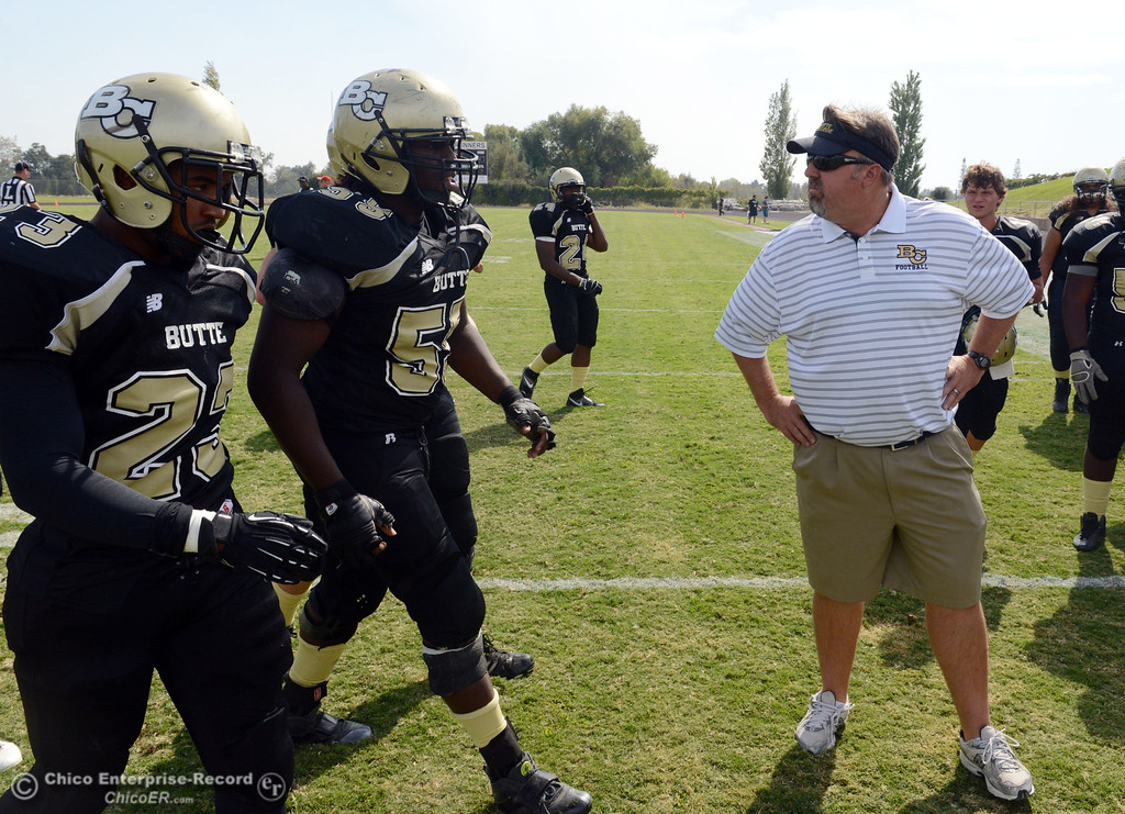 Description of . Butte College's #23 Mykah Hester (left) and #55 Dominique Harris (center) come off the field past head coach Jeff Jordan (right) against Delta College in the second quarter of their football game at Butte's Cowan Stadium Saturday, September 28, 2013, in Oroville, Calif.  (Jason Halley/Chico Enterprise-Record)