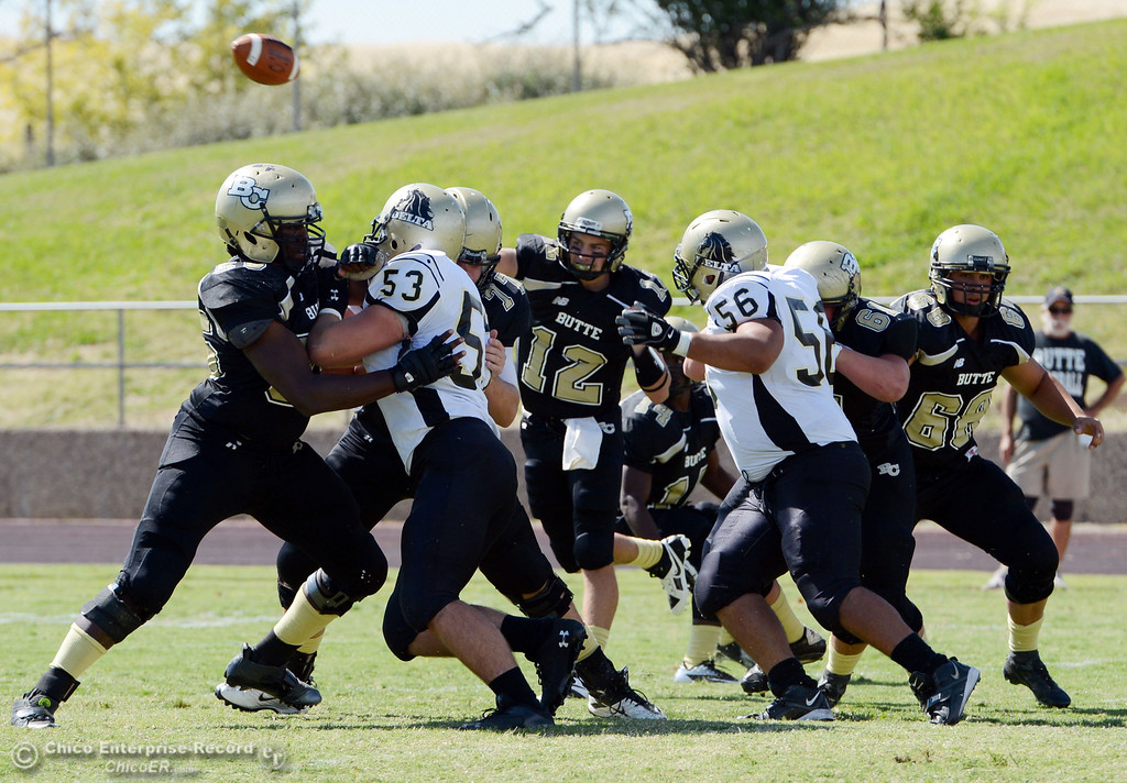 Description of . Butte College's #12 Thomas Stuart (center) throws a pass against Delta College in the first quarter of their football game at Butte's Cowan Stadium Saturday, September 28, 2013, in Oroville, Calif.  (Jason Halley/Chico Enterprise-Record)