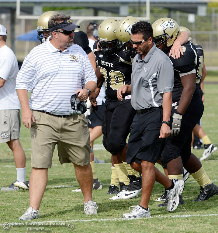 Description of . Butte College's coach Jeff Jordan (left) checks on #77 Scott Batchelder who was injured on the field against Delta College in the third quarter of their football game at Butte's Cowan Stadium Saturday, September 28, 2013, in Oroville, Calif.  (Jason Halley/Chico Enterprise-Record)