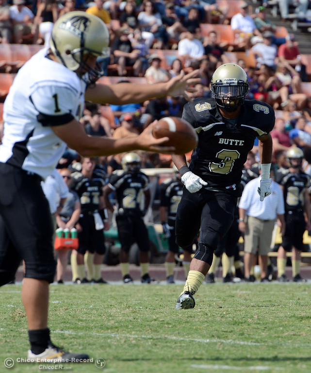 Description of . Butte College's #3 London Muse (right) pressures a punt against Delta College's #1 Kurtis Bettencourt (left) in the second quarter of their football game at Butte's Cowan Stadium Saturday, September 28, 2013, in Oroville, Calif.  (Jason Halley/Chico Enterprise-Record)