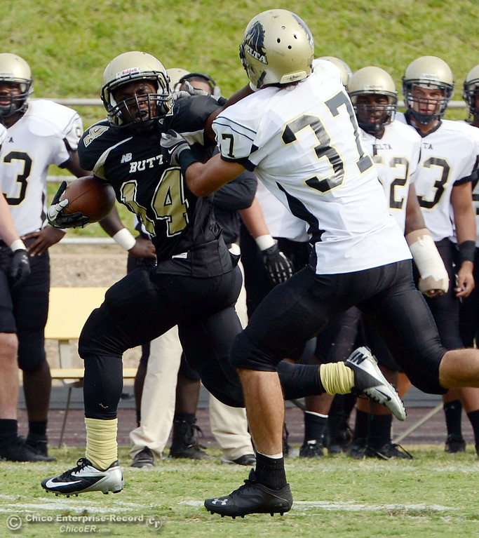Description of . Butte College\'s #14 Robert Frazier (left) is tackled against Delta College\'s #37 Chris Davi (right) in the fourth quarter of their football game at Butte\'s Cowan Stadium Saturday, September 28, 2013, in Oroville, Calif.  (Jason Halley/Chico Enterprise-Record)