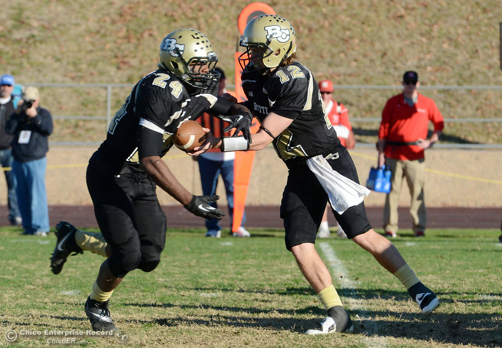 . Butte College\'s #12 Thomas Stuart (right) hands off to #24 Kendall Williams (left) against Fresno City College in the fourth quarter of their football game at Butte\'s Cowan Stadium Saturday, November 30, 2013 in Butte Valley, Calif.  (Jason Halley/Chico Enterprise-Record)