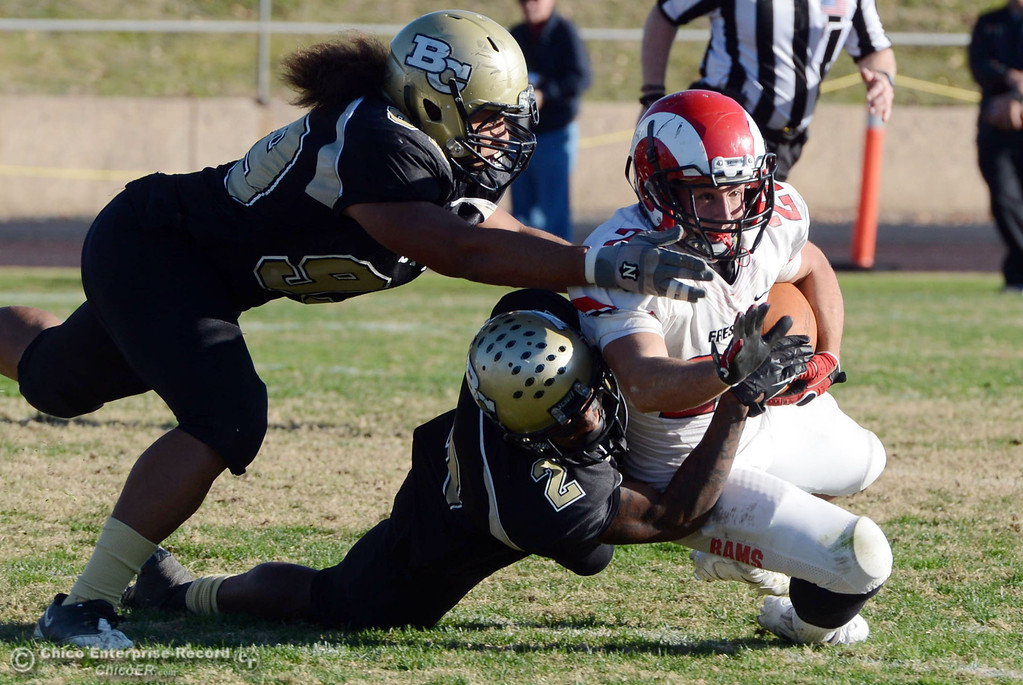 . Butte College\'s #99  Leopeni Siania (left) and #2 Deonte Flemings (center) tackle against Fresno City College\'s #22 Alek Mechikoff (right) in the fourth quarter of their football game at Butte\'s Cowan Stadium Saturday, November 30, 2013 in Butte Valley, Calif.  (Jason Halley/Chico Enterprise-Record)