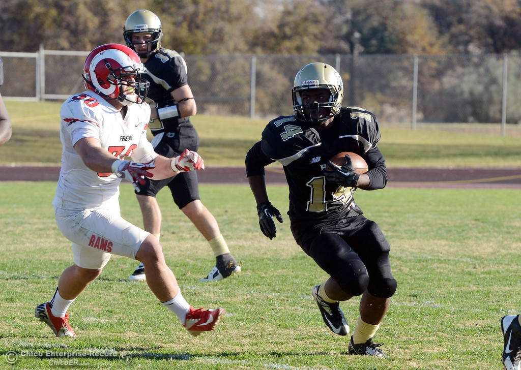 . Butte College\'s #14 Robert Frazier (right) rushes against Fresno City College\'s #30 Tyler Bates (left) in the third quarter of their football game at Butte\'s Cowan Stadium Saturday, November 30, 2013 in Butte Valley, Calif.  (Jason Halley/Chico Enterprise-Record)