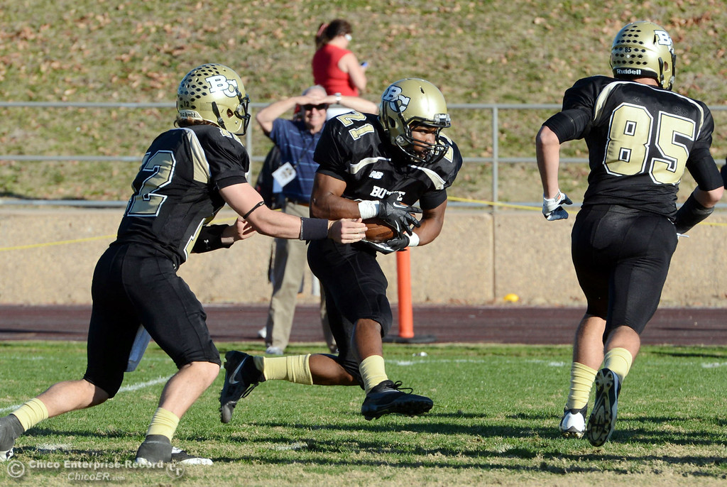 . Butte College\'s #12 Thomas Stuart (left) hands off to #21 Marvel Harris (right)  against Fresno City College in the fourth quarter of their football game at Butte\'s Cowan Stadium Saturday, November 30, 2013 in Butte Valley, Calif.  (Jason Halley/Chico Enterprise-Record)