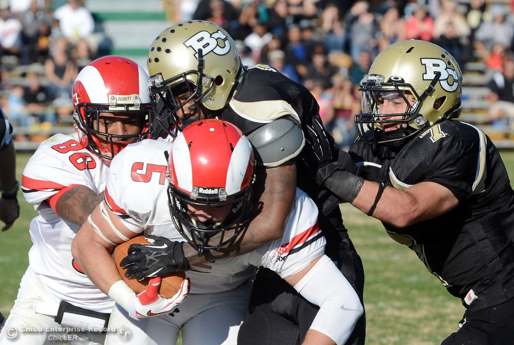 . Butte College\'s #2 Deonte Flemings (mid right) and #7 Ryan Holland (far right) tackles against Fresno City College\'s #5 Brayden Sanchez (mid left) near #86 Kevin Beckwith (far left) in the third quarter of their football game at Butte\'s Cowan Stadium Saturday, November 30, 2013 in Butte Valley, Calif.  (Jason Halley/Chico Enterprise-Record)