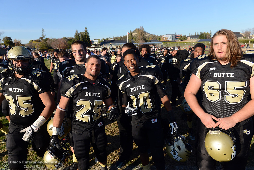 . Butte College\'s #95 Mark Rosenquist, #24 De\'Aundray Gooden,  #10 CJ Grice and #65 Tyler Anglin (left to right) celebrate their win against Fresno City College at the end of their football game at Butte\'s Cowan Stadium Saturday, November 30, 2013 in Butte Valley, Calif.  (Jason Halley/Chico Enterprise-Record)