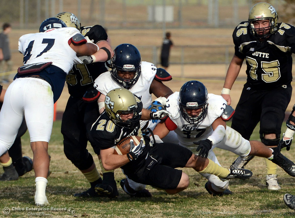 . Butte College\'s #20 Armand Bokitch (bottom) is tackled against Fullerton College\'s #37 Damien Zepeda (right) in the third quarter of their CCCAA football state championship final at Butte\'s Cowan Stadium Saturday, December 14, 2013 in Butte Valley, Calif. (Jason Halley/Chico Enterprise-Record)
