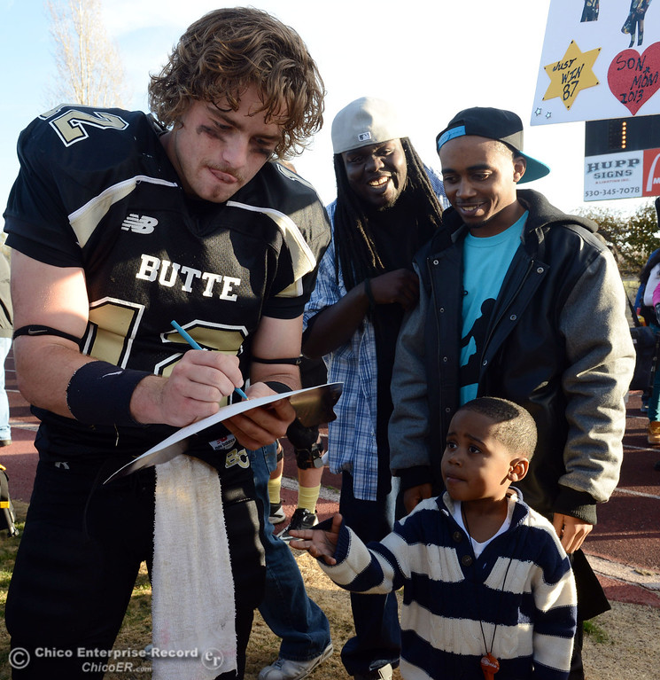 . Butte College\'s #12 Thomas Stuart (left) signs an autograph for Rasheed Shepherd Jr, 9 (bottom) with Rasheed Sheperd (right) looking on after their win against Fullerton College in the CCCAA football state championship final at Butte\'s Cowan Stadium Saturday, December 14, 2013 in Butte Valley, Calif. (Jason Halley/Chico Enterprise-Record)