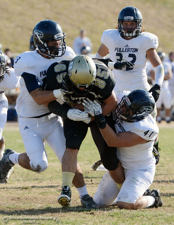 . Butte College\'s #85 Richard Murphy (center) is tackled against Fullerton College\'s #13 Alex Bernstein (left) and #41 Jordan Kessen (right) as #32 Justin Ownes (back) looks on in the first quarter of their CCCAA football state championship final at Butte\'s Cowan Stadium Saturday, December 14, 2013 in Butte Valley, Calif. (Jason Halley/Chico Enterprise-Record)