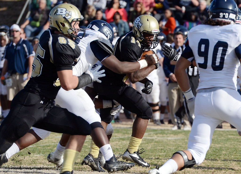 . Butte College\'s #14 Robert Frazier (right) is tackled against Fullerton College\'s #95 Andre McKinnon (left) in the second quarter of their CCCAA football state championship final at Butte\'s Cowan Stadium Saturday, December 14, 2013 in Butte Valley, Calif. (Jason Halley/Chico Enterprise-Record)
