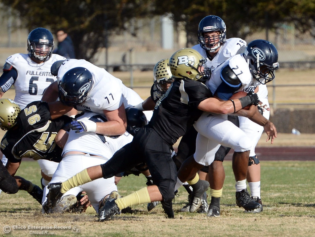 . Butte College\'s #7 Ryan Holland (left) tackles against Fullerton College\'s #27 Ryan Byrd (right) in the first quarter of their CCCAA football state championship final at Butte\'s Cowan Stadium Saturday, December 14, 2013 in Butte Valley, Calif. (Jason Halley/Chico Enterprise-Record)