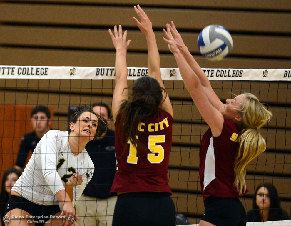 Description of . Butte College's #12 Callie Flood (left) spikes against Sac City College' #15 Raven Balafoutis (center) and #8 Kylee North (right) in the second game of their women's volleyball match at Butte's Cowan Gym Wednesday, September 25, 2013, in Oroville, Calif.  (Jason Halley/Chico Enterprise-Record)