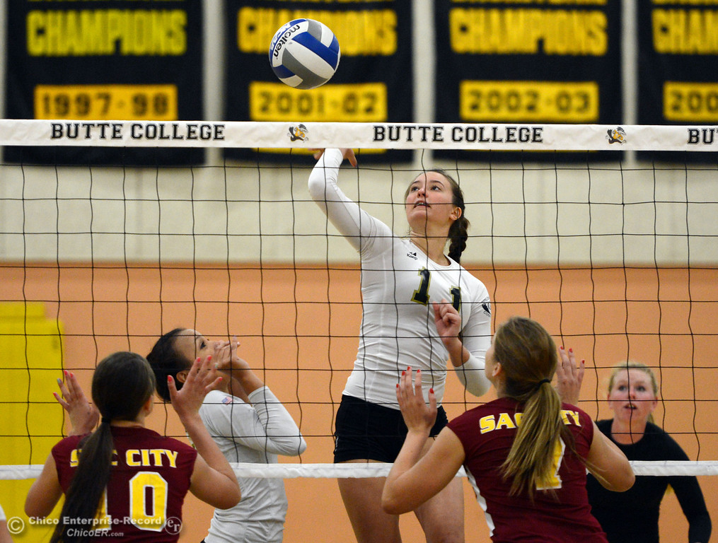 Description of . Butte College\'s #11 Brooke Silverman spikes against Sac City College in the first game of their women\'s volleyball match at Butte\'s Cowan Gym Wednesday, September 25, 2013, in Oroville, Calif.  (Jason Halley/Chico Enterprise-Record)