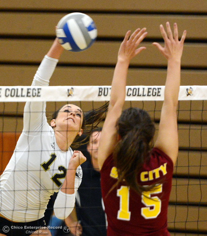 Description of . Butte College's #12 Callie Flood (left) spikes against Sac City College' #15 Raven Balafoutis (right) in the second game of their women's volleyball match at Butte's Cowan Gym Wednesday, September 25, 2013, in Oroville, Calif.  (Jason Halley/Chico Enterprise-Record)