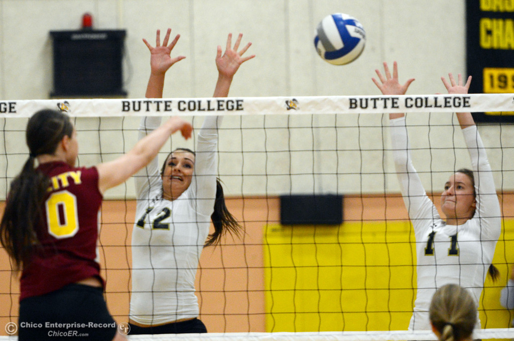 Description of . Butte College's #12 Callie Flood (center) and #11 Brooke Silverman (right) attempt to block against Sac City College' #10 Keeley Franz (left) in the first game of their women's volleyball match at Butte's Cowan Gym Wednesday, September 25, 2013, in Oroville, Calif.  (Jason Halley/Chico Enterprise-Record)