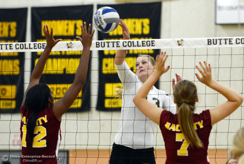 Description of . Butte College's #13 Emilie Aase (center) spikes against Sac City College's #12 Akeya Maddox (left) and #7 Macyn Carpenter (right) in the second game of their women's volleyball match at Butte's Cowan Gym Wednesday, September 25, 2013, in Oroville, Calif.  (Jason Halley/Chico Enterprise-Record)