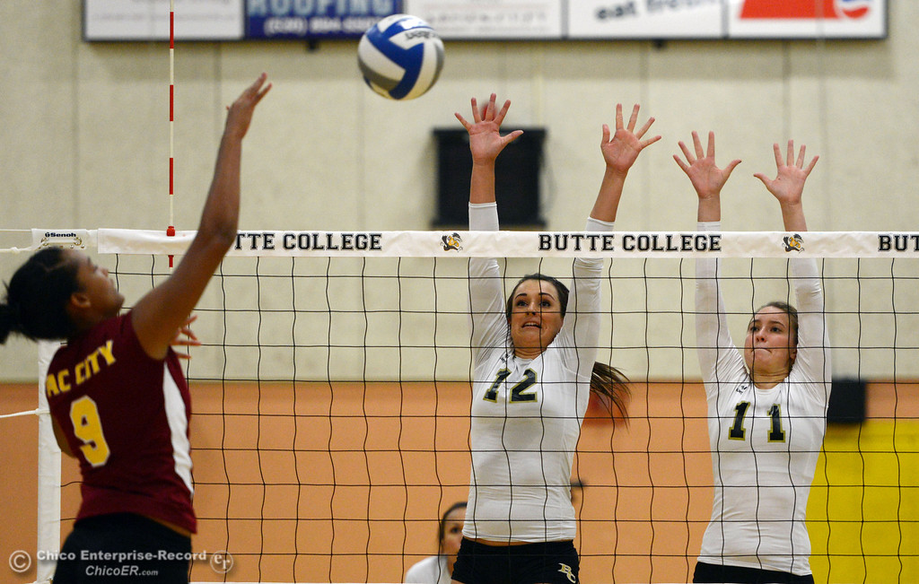 Description of . Butte College's #12 Callie Flood (center) and #11 Brooke Silverman (right) attempt to block against Sac City College' #9 Elliza North (left) in the first game of their women's volleyball match at Butte's Cowan Gym Wednesday, September 25, 2013, in Oroville, Calif.  (Jason Halley/Chico Enterprise-Record)