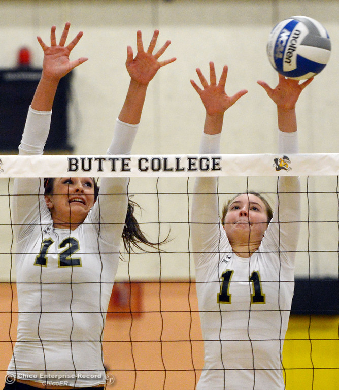 Description of . Butte College's #12 Callie Flood (left) and #11 Brooke Silverman (right) attempt to block against Sac City College' #9 Elliza North (not seen) in the first game of their women's volleyball match at Butte's Cowan Gym Wednesday, September 25, 2013, in Oroville, Calif.  (Jason Halley/Chico Enterprise-Record)