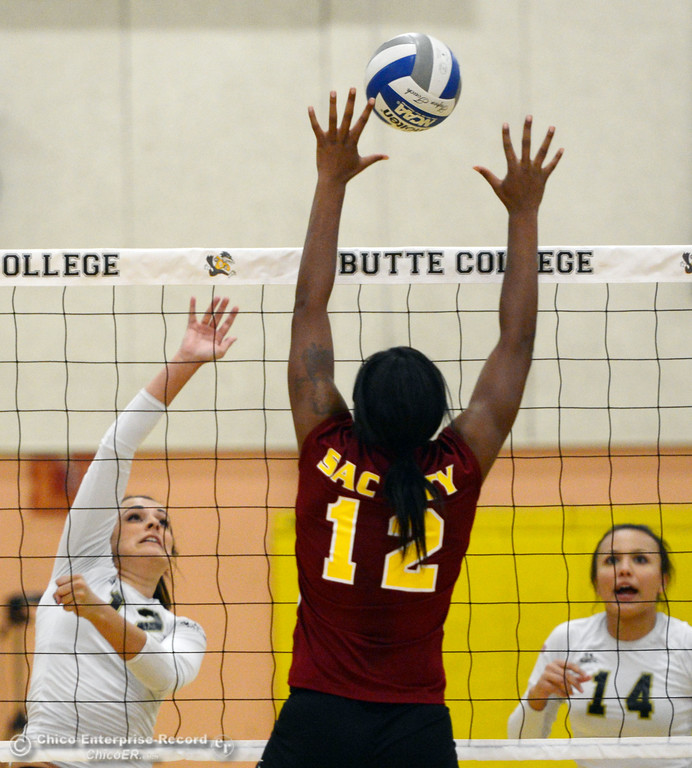 Description of . Butte College's #12 Callie Flood (left) spikes against Sac City College's #12 Akeya Maddox (right) in the first game of their women's volleyball match at Butte's Cowan Gym Wednesday, September 25, 2013, in Oroville, Calif.  (Jason Halley/Chico Enterprise-Record)