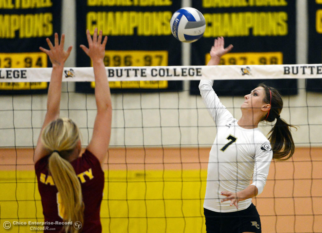 Description of . Butte College\'s #7 Taylor Johnson (right) spikes against Sac City College\'s #8 Kylee Hardy (left) in the first game of their women\'s volleyball match at Butte\'s Cowan Gym Wednesday, September 25, 2013, in Oroville, Calif.  (Jason Halley/Chico Enterprise-Record)