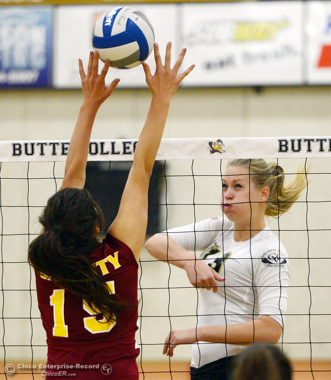 Description of . Butte College's #13 Emilie Aase (right) spikes against Sac City College's #15 Raven Balafoutis (left) in the first game of their women's volleyball match at Butte's Cowan Gym Wednesday, September 25, 2013, in Oroville, Calif.  (Jason Halley/Chico Enterprise-Record)